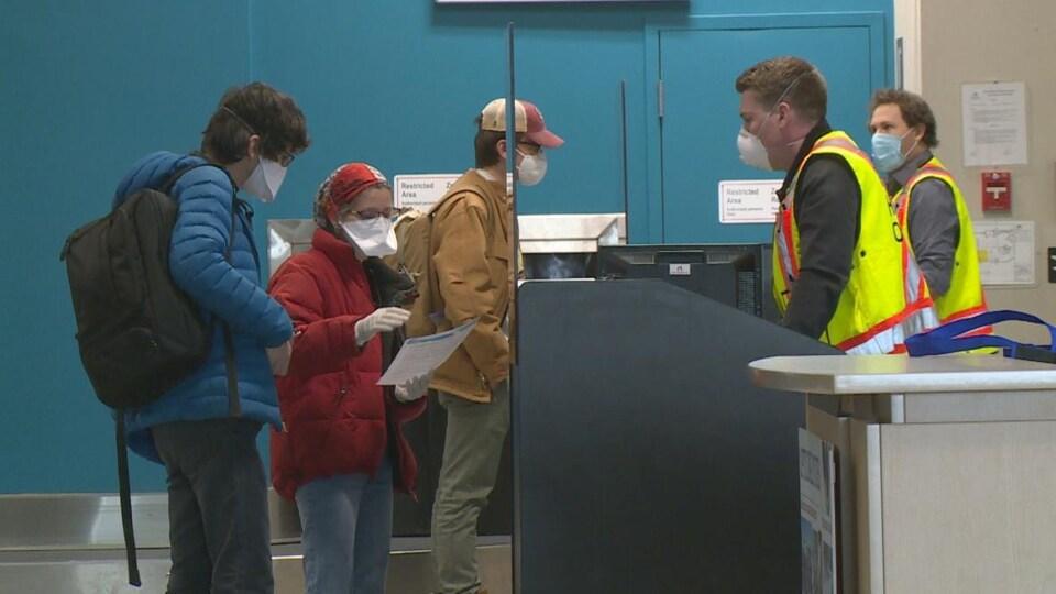 Des voyageurs portant un masque attendent en file à l'aéroport de Yellowknife.