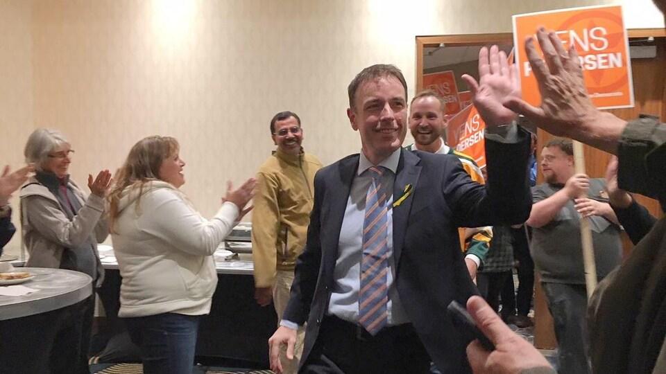 Le gagnant de l'élection tape dans la main d'un partisan. On aperçoit le chef du parti, Ryan Meili, derrière lui. Les deux sont applaudis à leur entrée dans la pièce.
