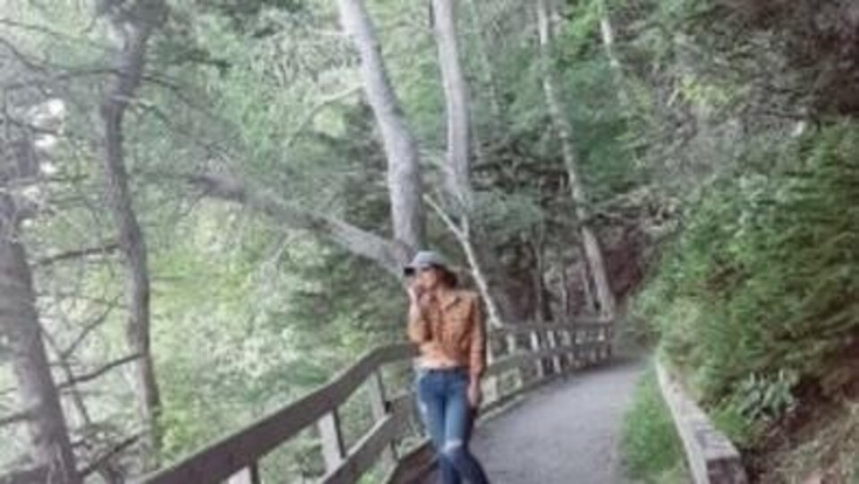 Yesenia Flores se trouve au milieu d'un sentier dans le bois.