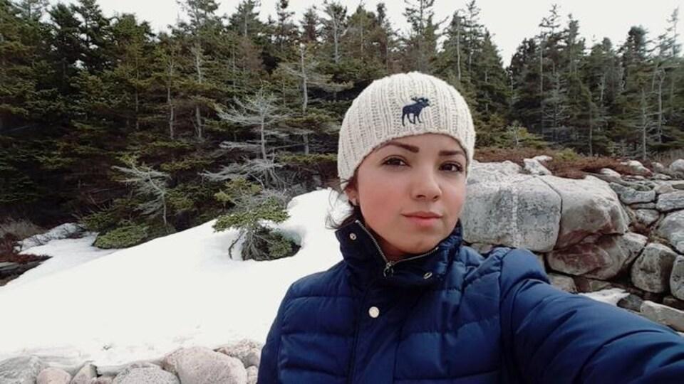Image d'une jeune femme prenant un égoportrait devant plusieurs sapins enneigés