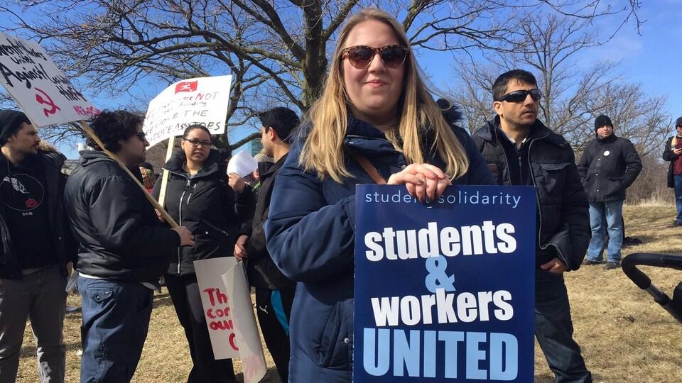 Photo d'une étudiante qui tient une affiche disant que les étudiants et les travailleurs sont unis.