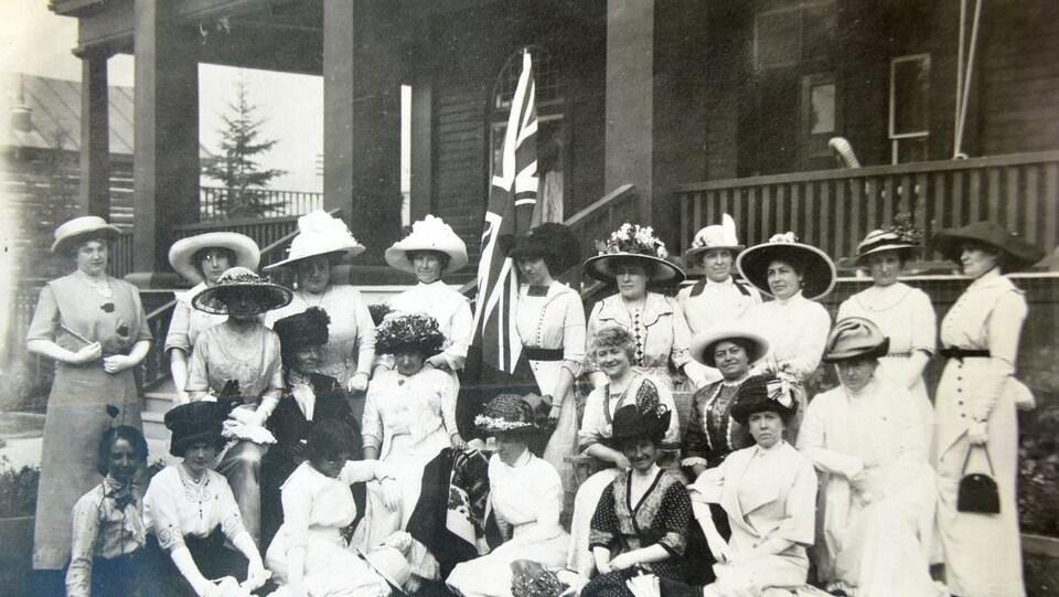 Photo en noir et blanc d'un groupe de femmes avec un drapeau britannique.
