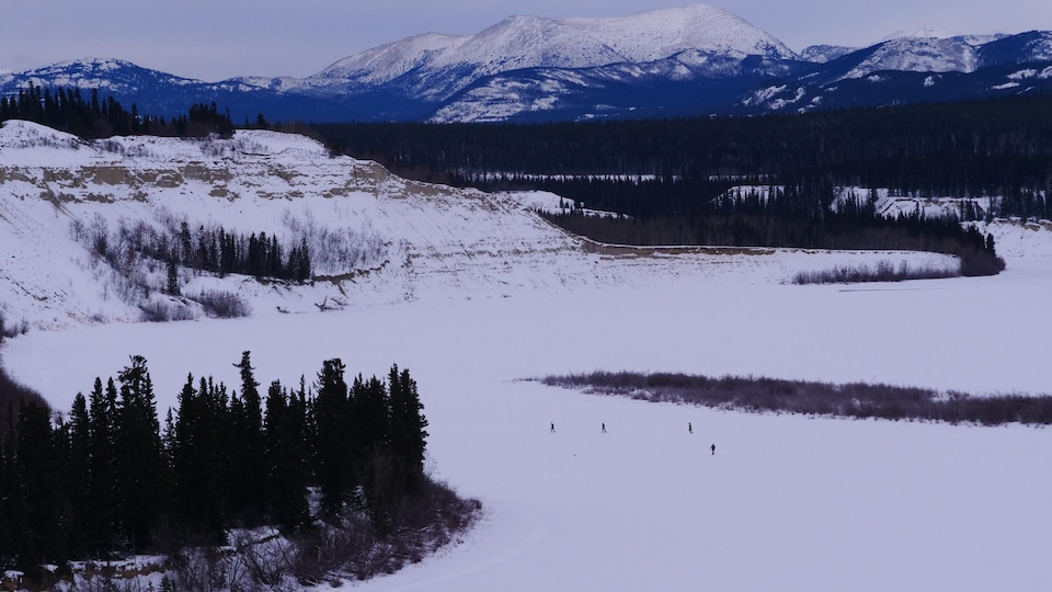 Des participants sur la piste vus de loin avec le paysage de montagnes en arrière-plan.