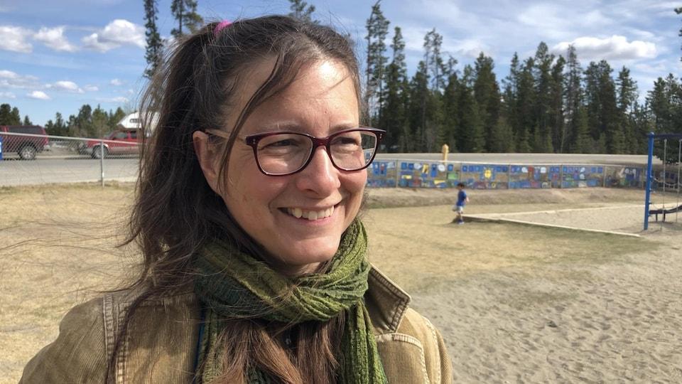 Une femme sourit devant la caméra dans une cour d'école.