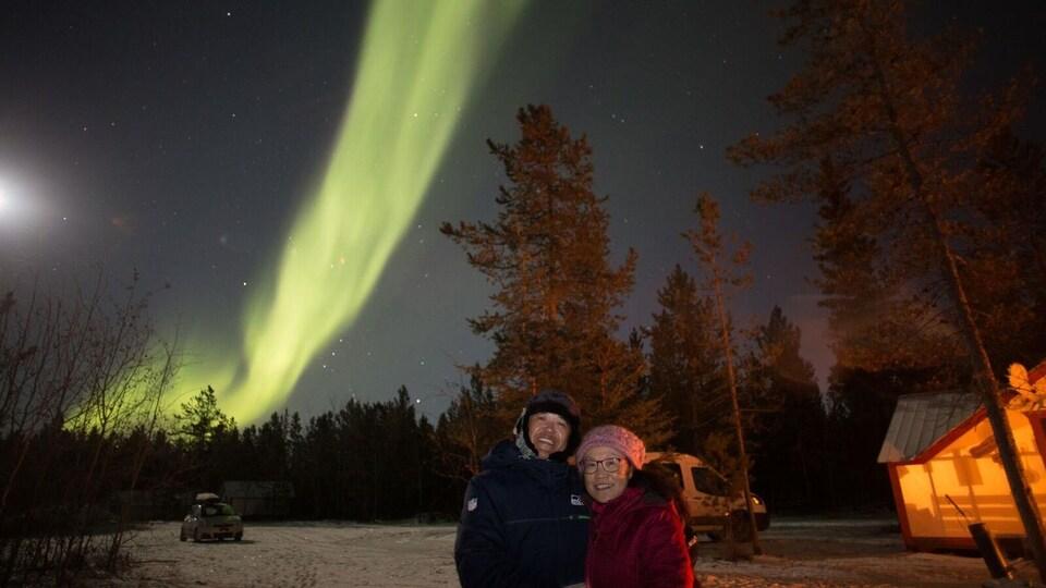 Des touristes sous les aurores boréales.