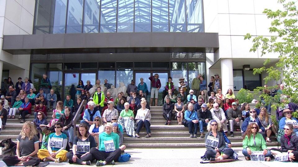 Des dizaines de personnes portant des affiches autour du cou sont assises dehors devant un bâtiment.