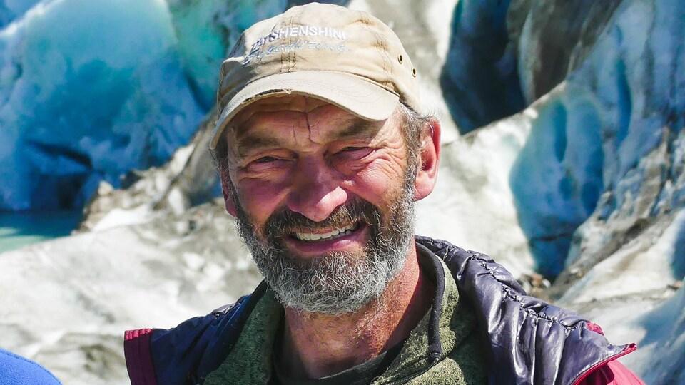 Robert Daffe sourit à la caméra, un glacier en arrière-plan.