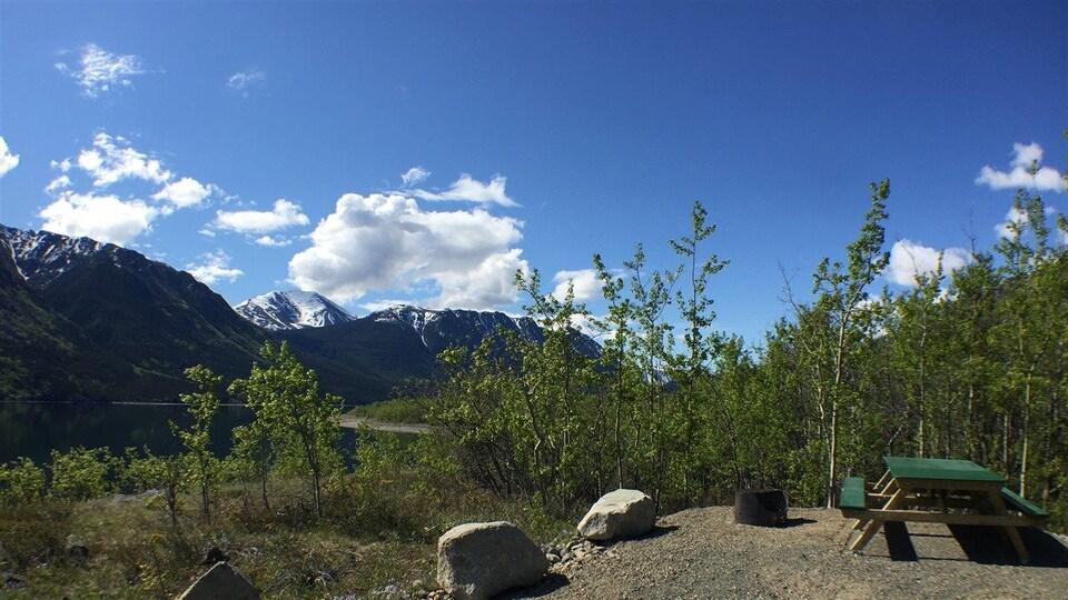 Un des sites du camping Conrad avec en arrière-plan des montagnes.