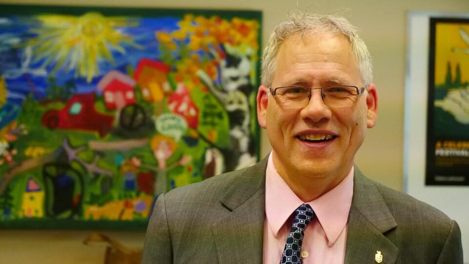 Plan moyen de John Streiker debout devant une toile souriant à la caméra.