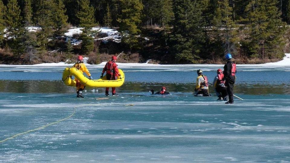 Des gens en tenue étanche marchent sur la glace en bordure de l'eau.
