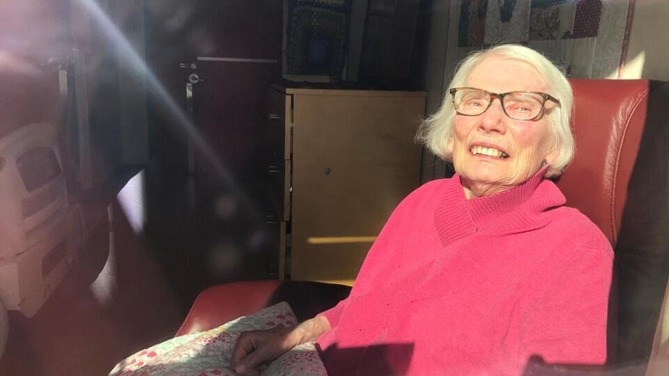 Une dame assise de l'autre côté d'une fenêtre.