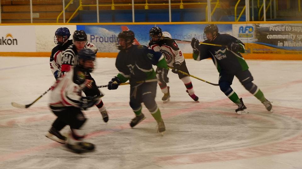 Des joueurs se disputent la rondelle sur la glace autour d'un arbitre.