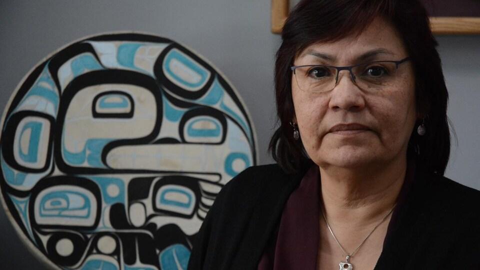 Une femme sourit devant une oeuvre d'art autochtone sur un mur.