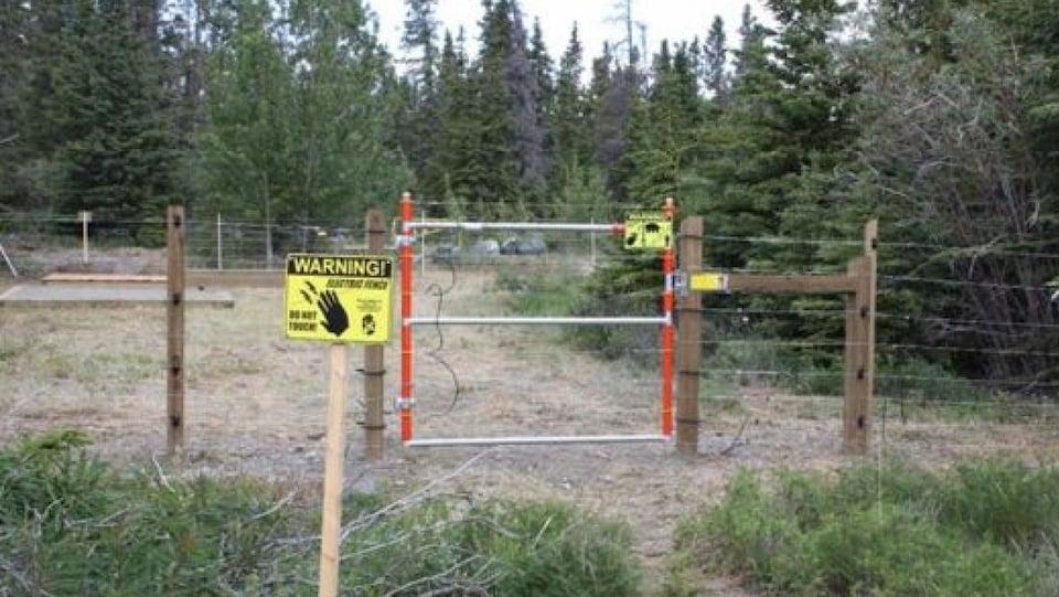 Une clôture avec des panneaux d'avertissement.
