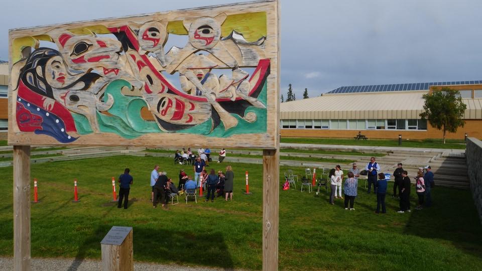 Des gens sont rassemblés sur une pelouse derrière une oeuvre d'art autochtone.