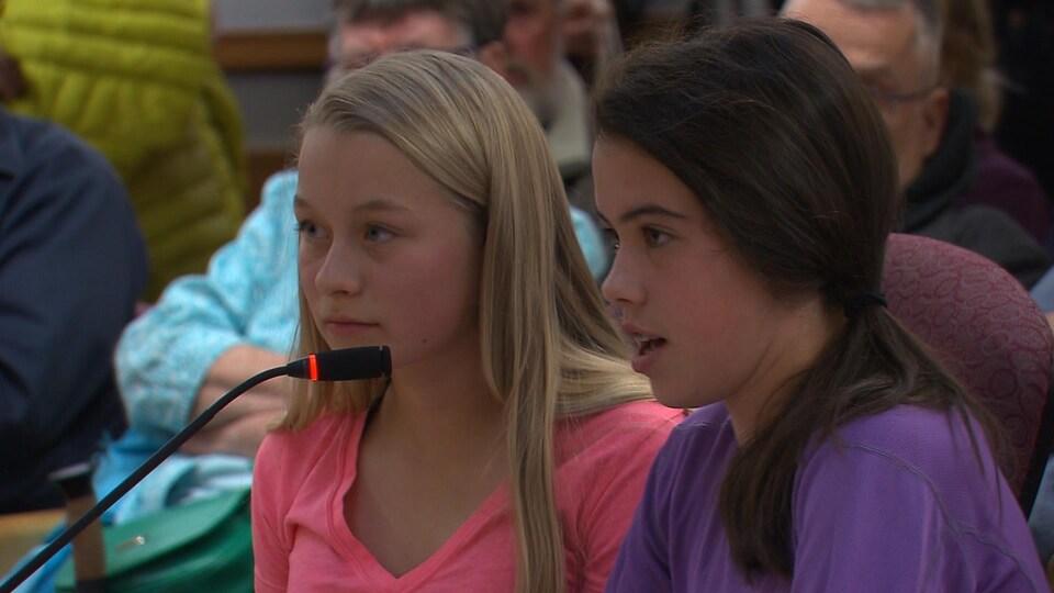 Plan moyen de Sophie Molgat debout derrière un micro. À sa droite, une autre jeune intervenante.