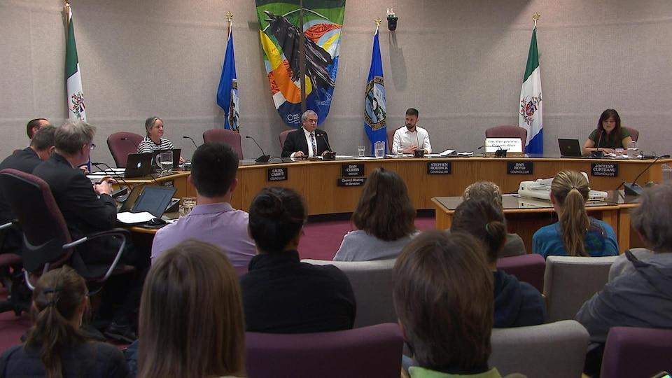 Des gens assis regardent des représentants assis à une grande table longue.