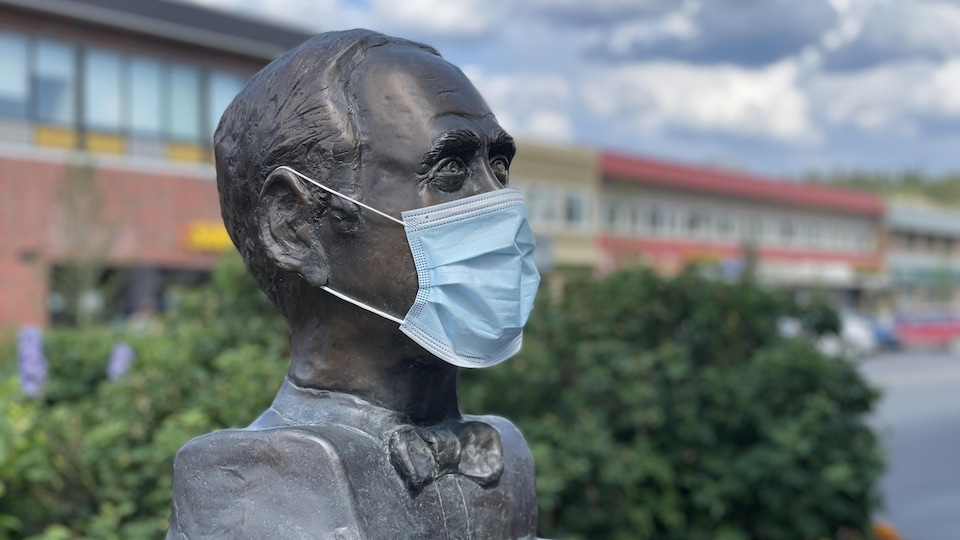 Le buste de l'auteur Pierre Berton porte un masque sur la rue Main à Whitehorse.