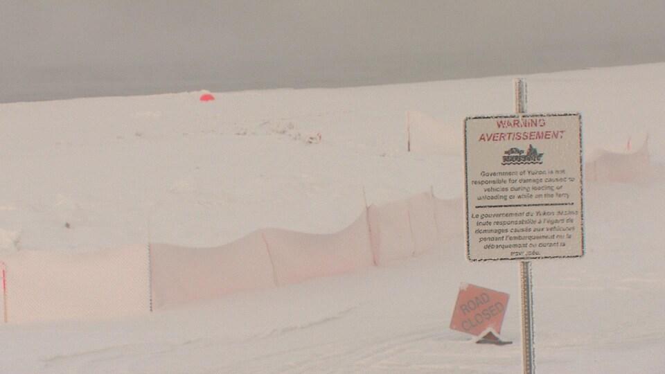 Étendue d'eau ouverte derrièere une rive glacée et une pancarte indiquant un traversier.