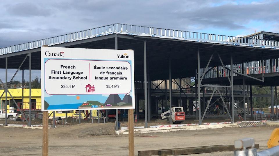 Grande affiche devant un chantier de construction.