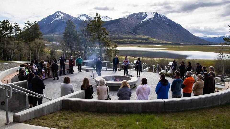 Plan large de la cérémonie à Carcross avec vue sur un lac et les montagnes.