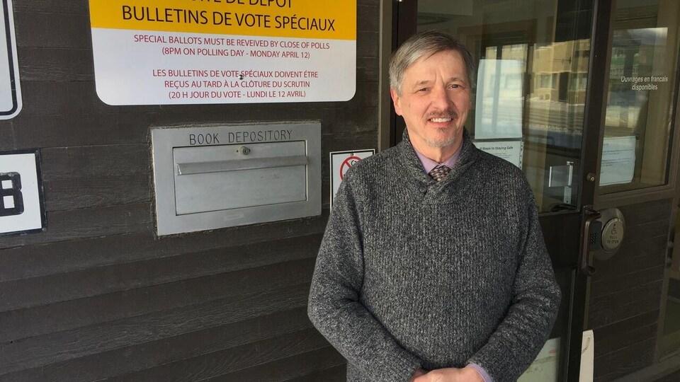 Maxwell Harvey, le directeur général des élections du Yukon devant la boîte de dépôt.