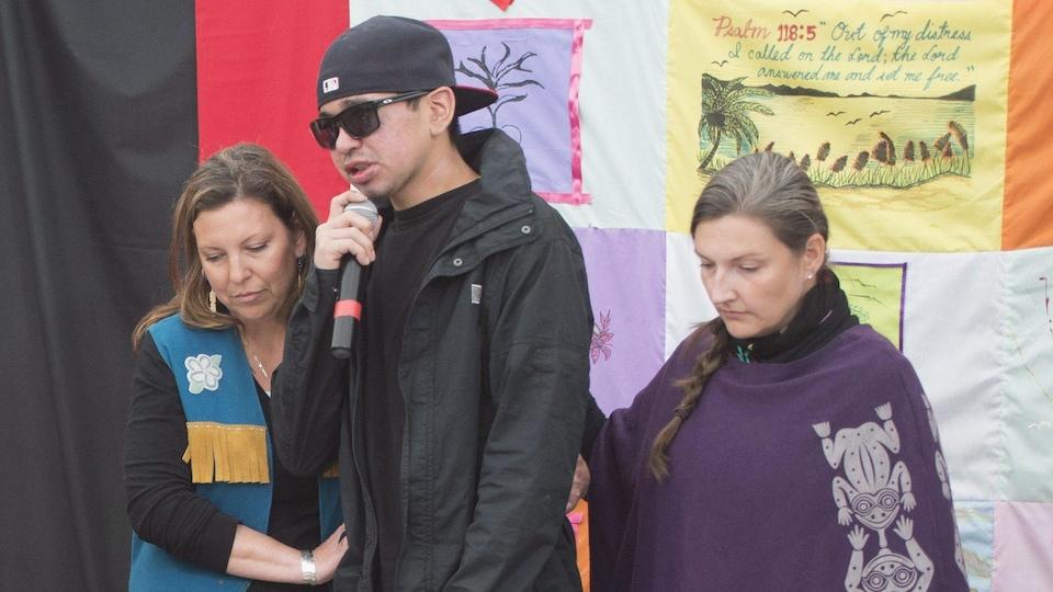 Un jeune homme avec des lunettes fumées au micro.
