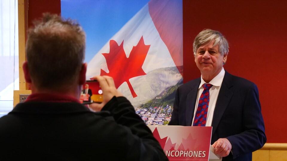 Un homme derrière un lutrin et devant des banderoles se fait filmer.