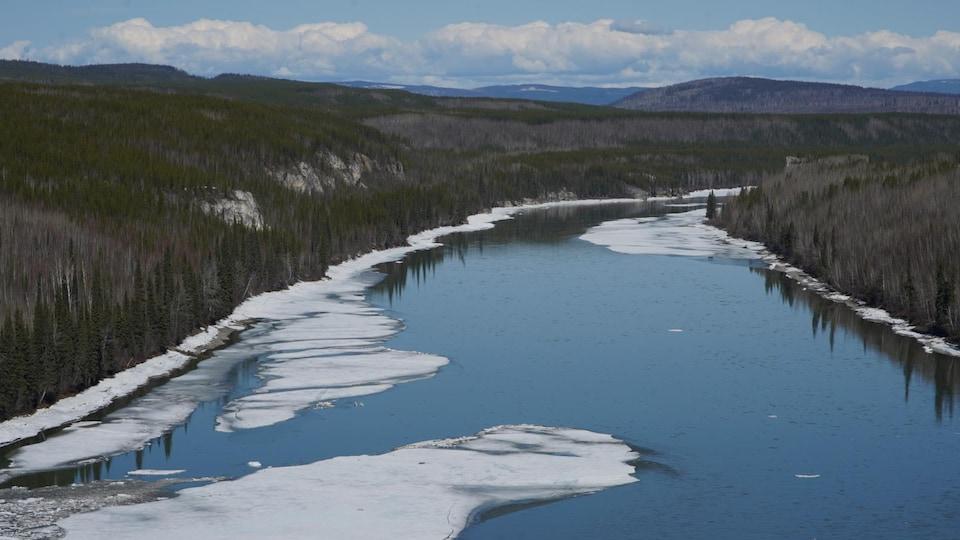 Un fleuve coule au milieu de la forêt boréale.