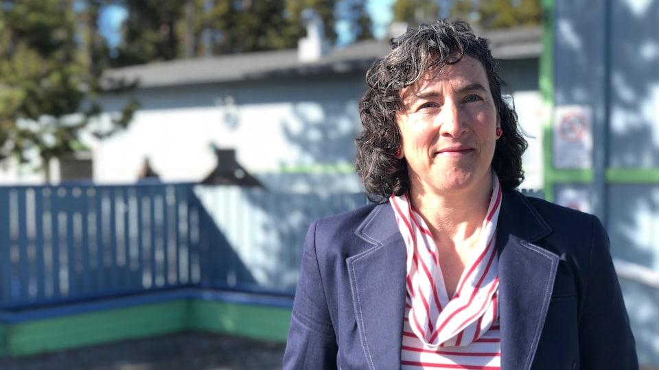 Plan moyen de Louise-Hélène Villeneuve debout à l'extérieur sourit à la caméra.