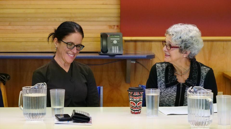 Deux femmes échangent quelques mots en se regardant.