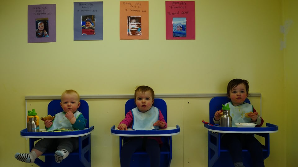 Trois enfants mangent dans des chaises accrochées au mur.