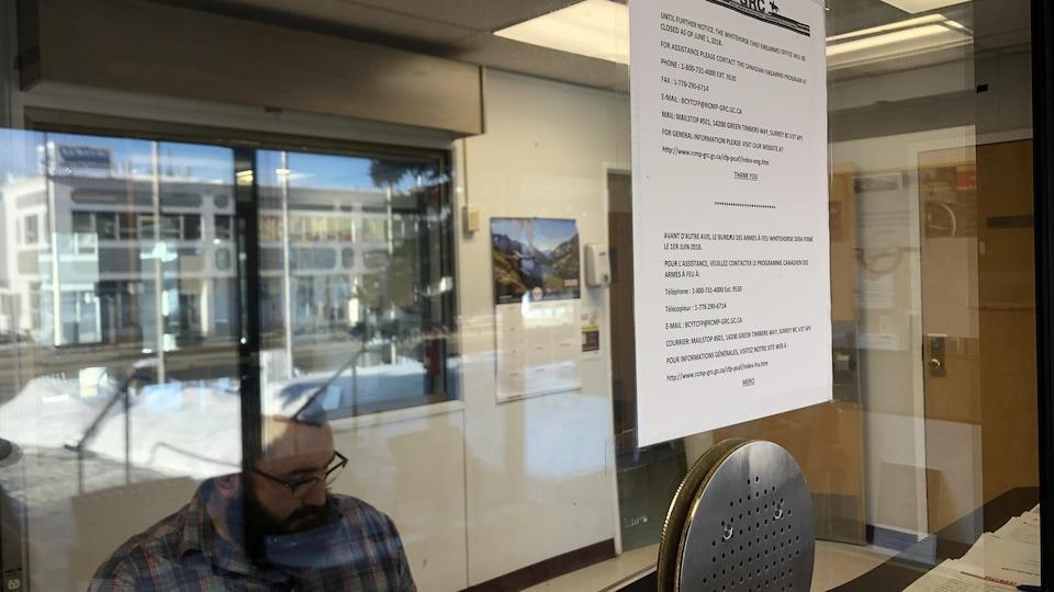 Un employé derrière une vitre recouverte d'une affiche.
