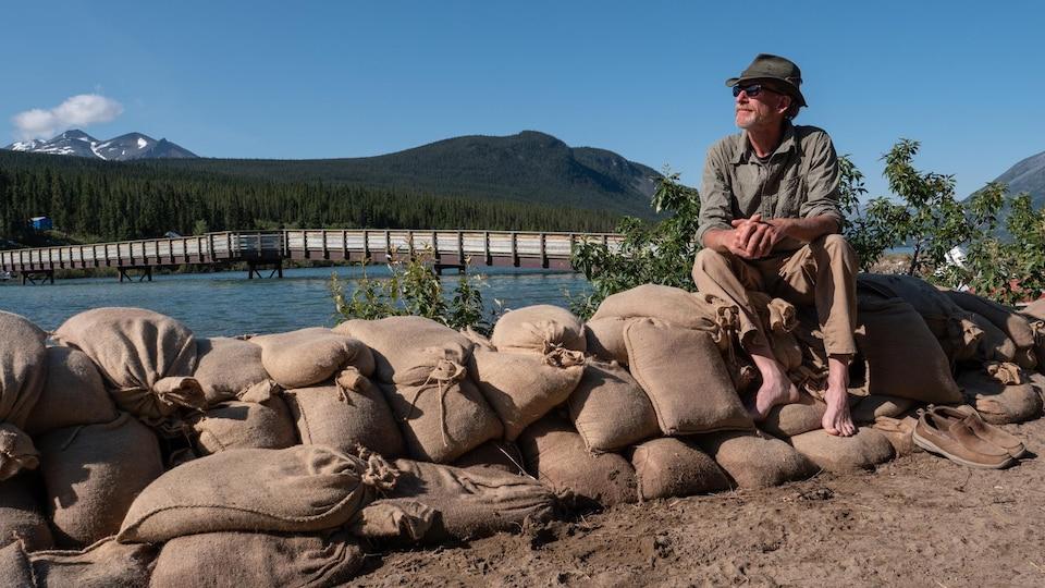 Dan Patterson est assis sur des sacs de sable devant le lac Bennett.