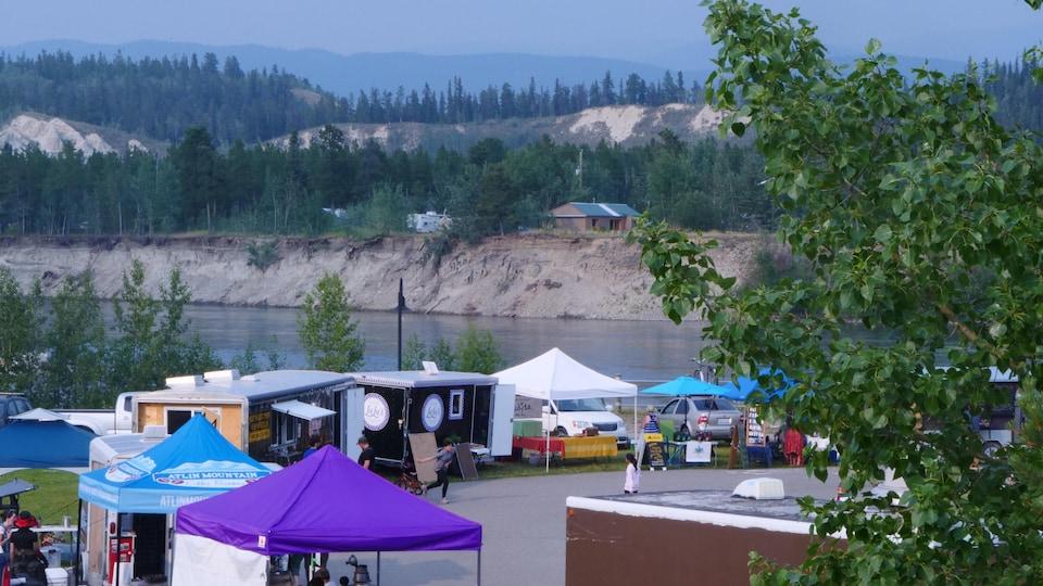 Des tentes et kiosques sont installés devant un cours d'eau.
