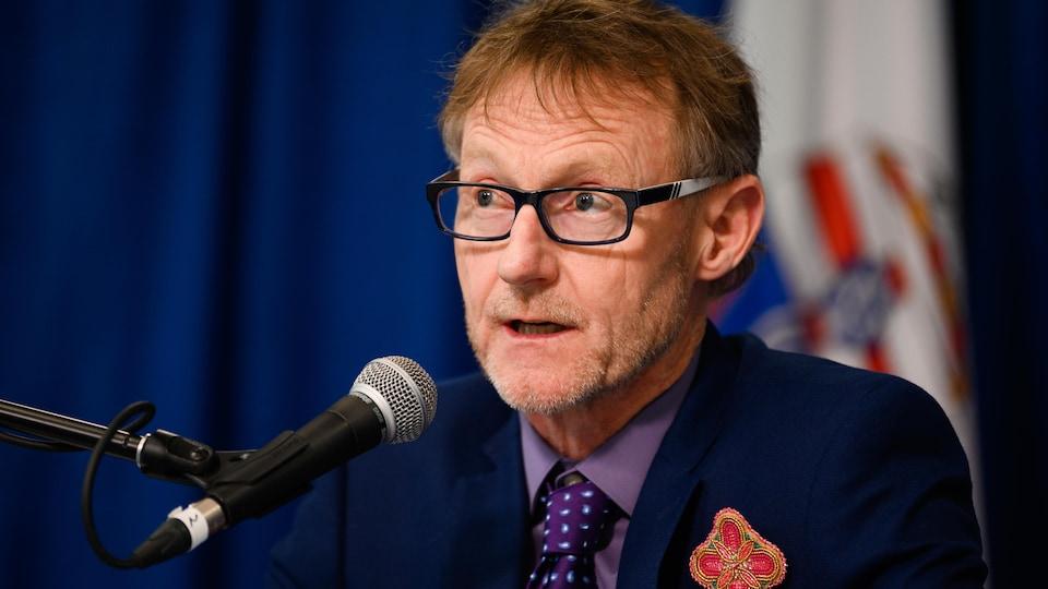 Brendan Hanley derrière un micro, lors d'une conférence de presse.