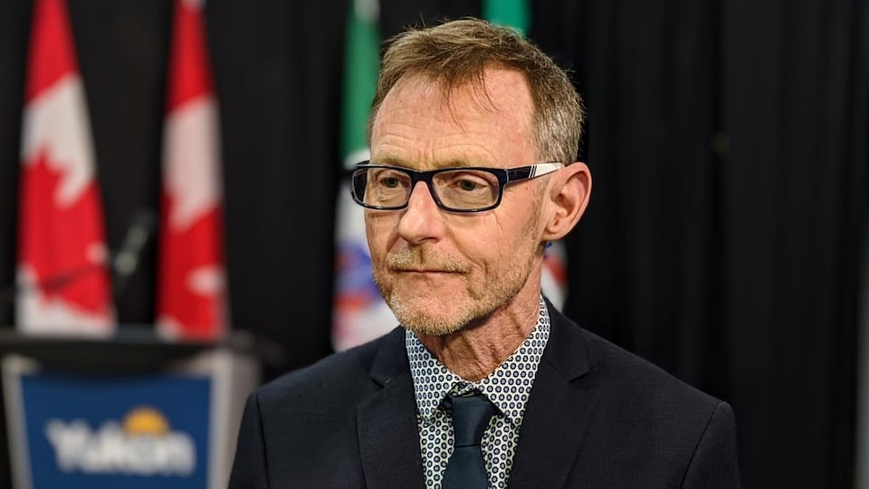 Brendan Hanley en conférence de presse devant des drapeaux du Canada et du Yukon.