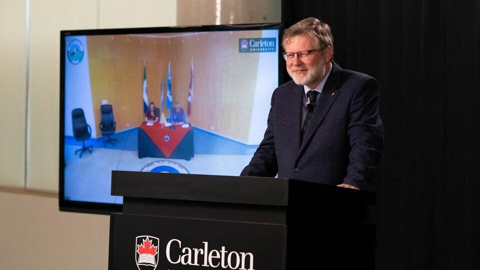 Christopher Burn derrière un podium et devant un écran où on aperçoit des gens à une table.