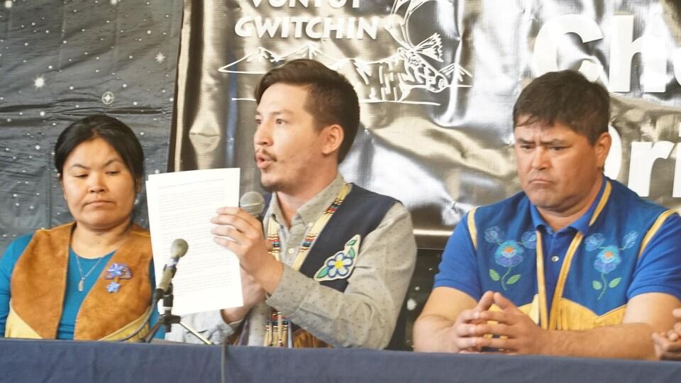 Un homme tient un document entre ses mains en parlant dans un micro aux côtés d'un homme et d'une femme assis à une table.