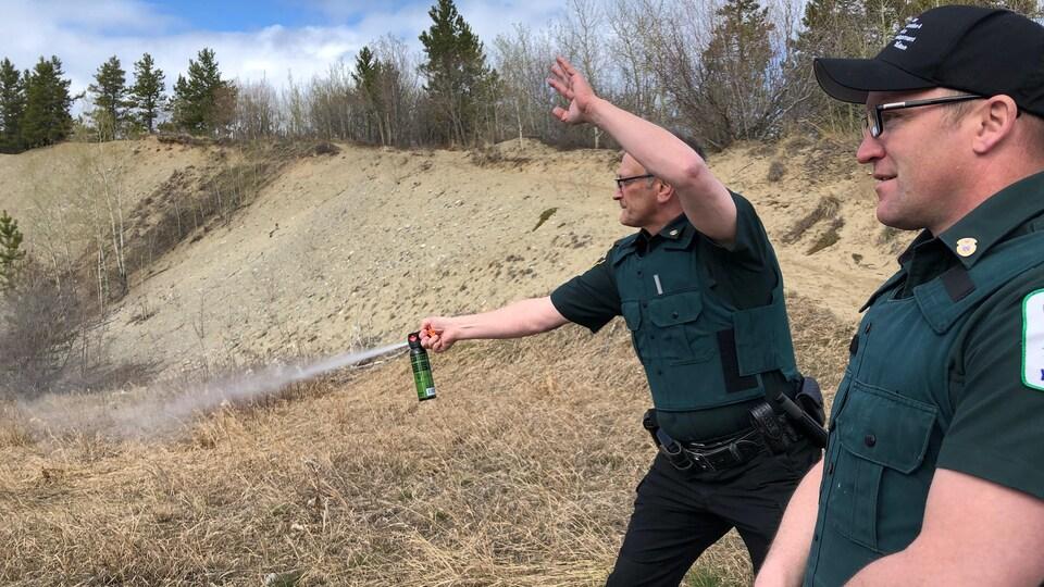 Un homme en uniforme à l'extérieur vaporise une bombonne dans les airs.
