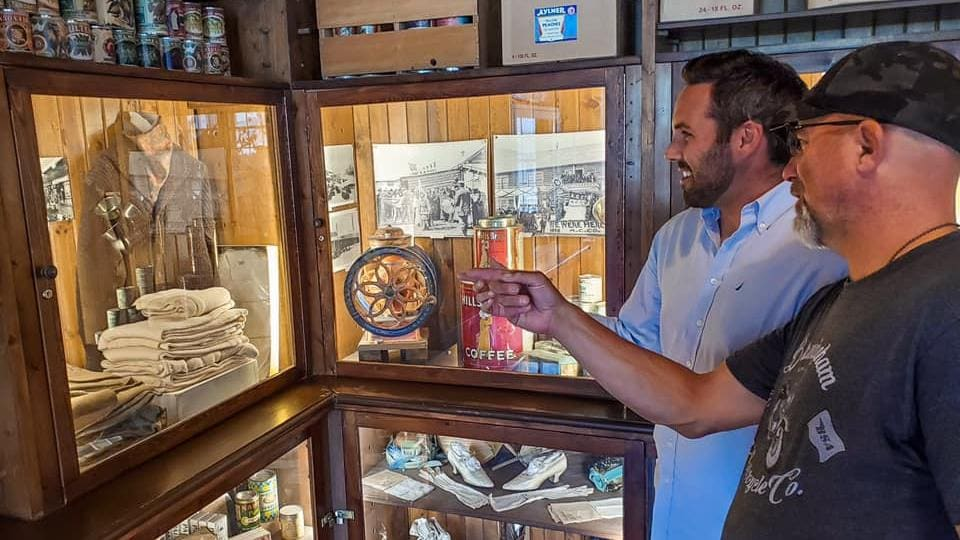 Deux hommes regardent des objets anciens dans une armoire.