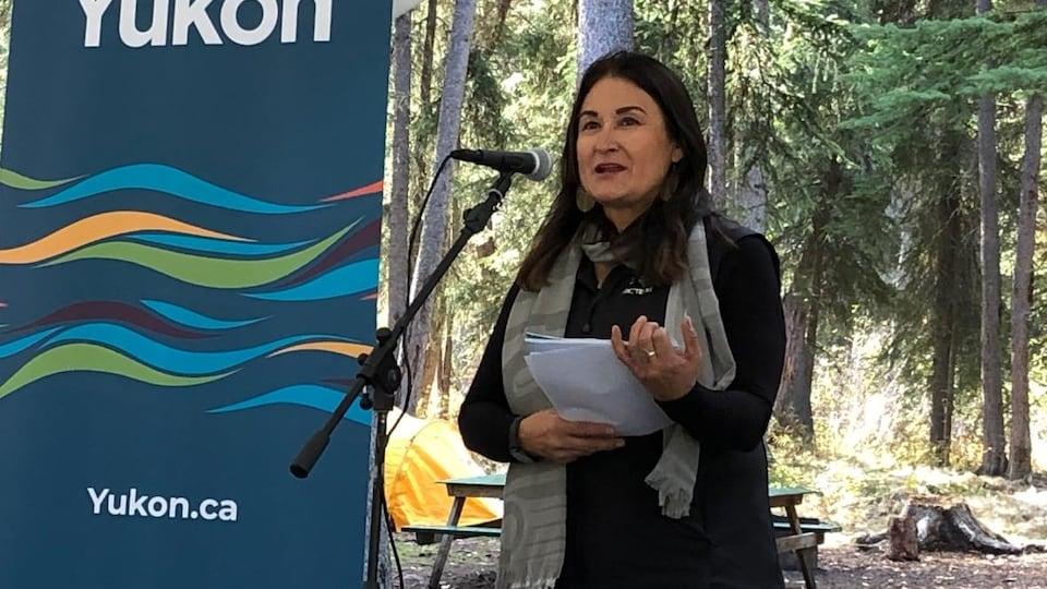 Pauline Frost derrière un micro en pleine forêt.