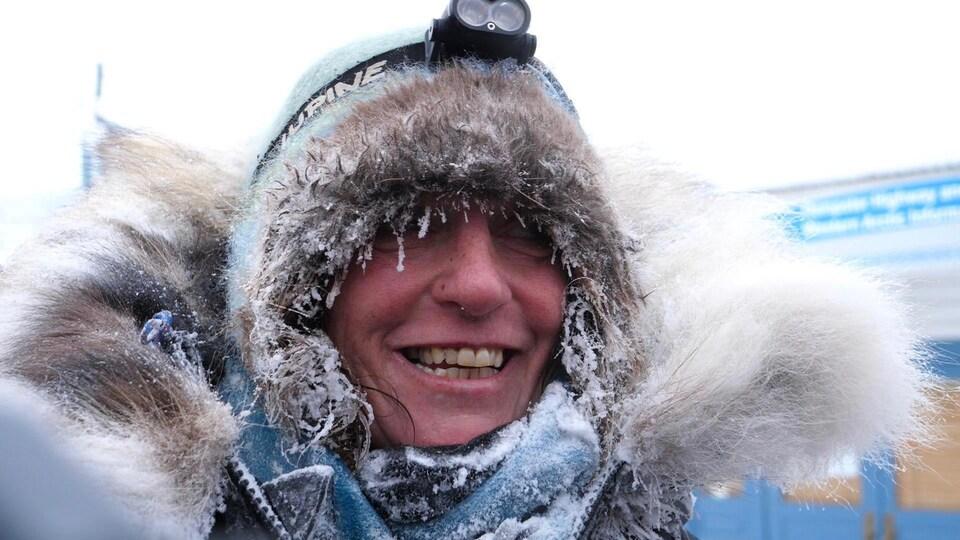 Michelle Phillips sourit en hiver alors que la fourrure de son manteau et ses cheveux sont gelés.
