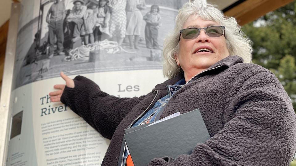 Anne-Marie Miller montre un panneau explicatif avec une photo de son grand-père, Frank Slim.