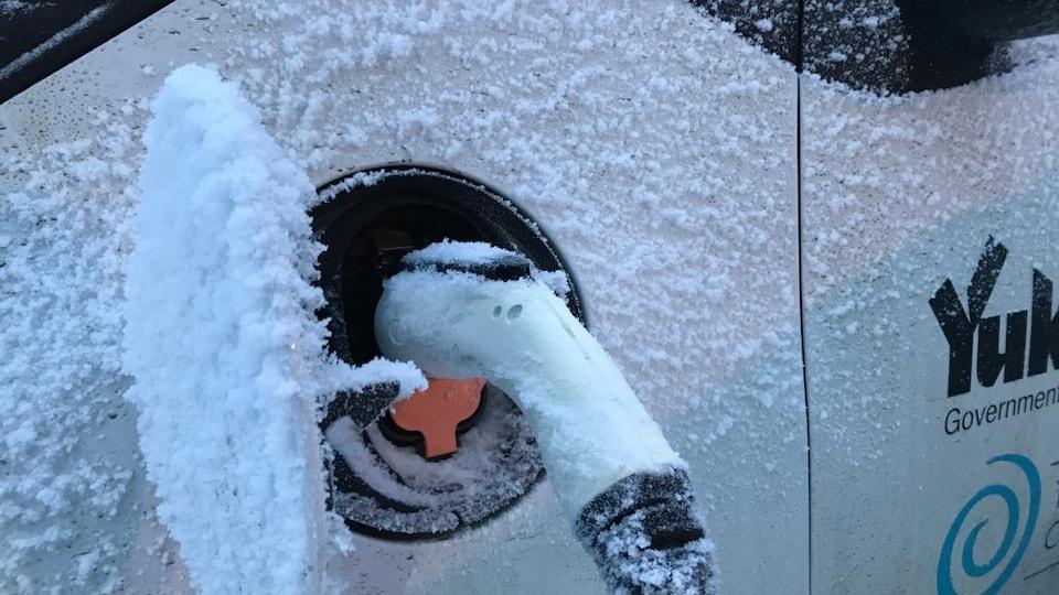 Une voiture électrique en recharge en hiver.