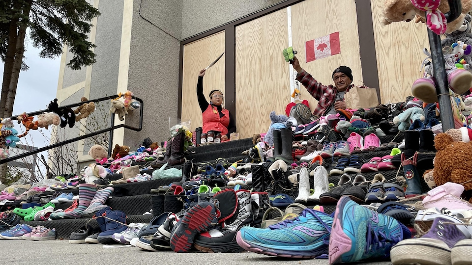 Deux personnes sont assises entre les chaussures d'enfants devant l'église les bras dans les airs.