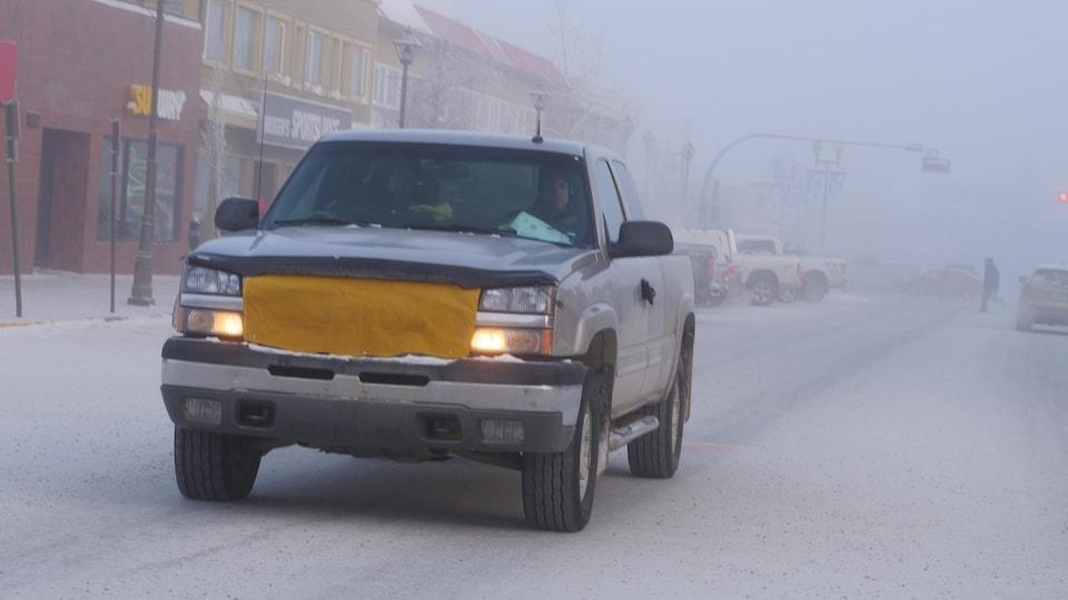Une camionnette sur la rue dont la devanture est couverte d'une bâche.