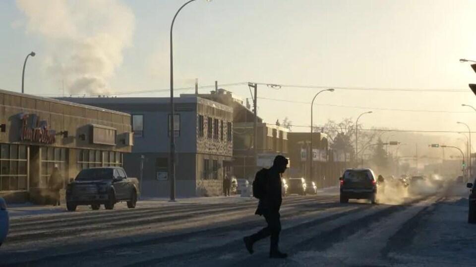 une personne tranverse la rue, sous la neige.