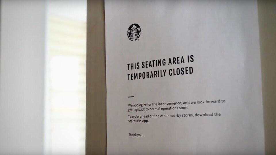 Une affiche collée dans une fenêtre d'un café Starbucks indique aux clients qu'ils ne peuvent plus consommer dans l'espace commun.