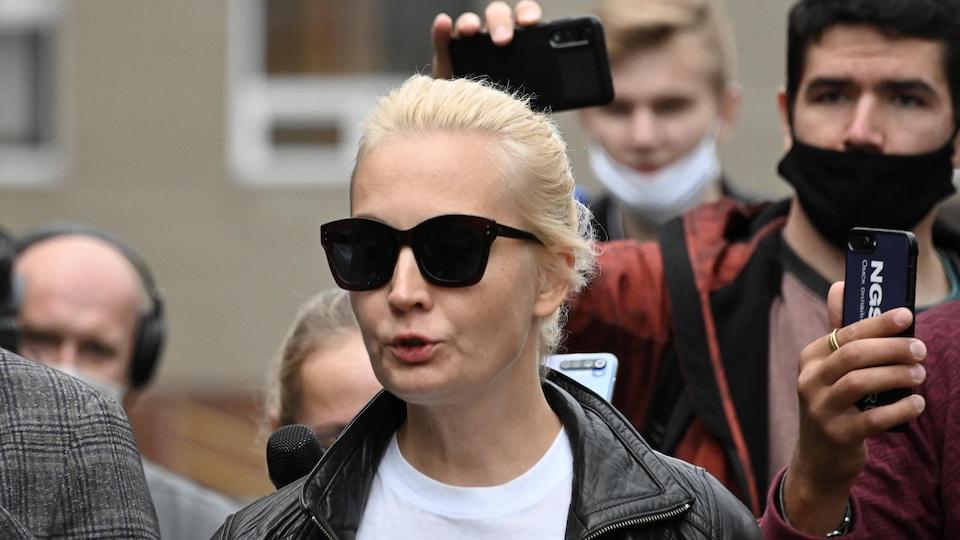 Ioulia Navalnaïa, portant des lunettes fumées, est entourée de journalistes.